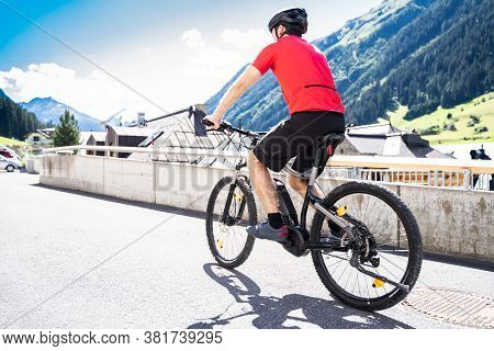 Man Riding E Bike Bicycle In City. Electric Bike In Summer