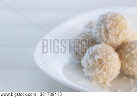 Coconut Candy Balls In Plate Covered With Chocolate And Shredded Coconut On Rustic Wooden Background