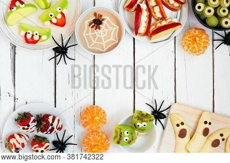 Healthy Halloween Fruit Snacks. Assortment Of Fun, Spooky Treats. Above View Double Border Over A Wh