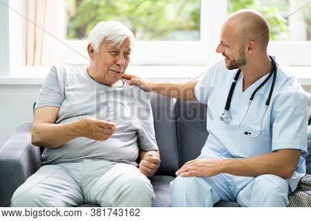 Old Senior Home Care Patient With Nurse At Home