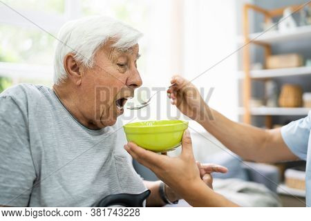 Hungry Elder Patient Being Feed At Nursing Home