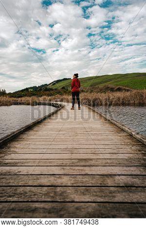 Girl Walking On Wooden Walkway On Peka Peka Wetlands, Hawke's Bay, New Zealand. Vertical Photo