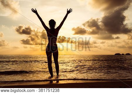 Womans Silhouette With Raised Arms Against Calm Sunset Beach