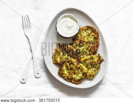 Potatoes, Zucchini, Herbs Fritters With Sour Cream Sauce On A Light Background, Top View. Delicious