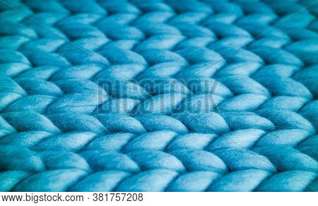 Background. Knitted Fabric Made Of Blue Merino Wool. Large Weave. Denim. Pattern Of Pigtails.