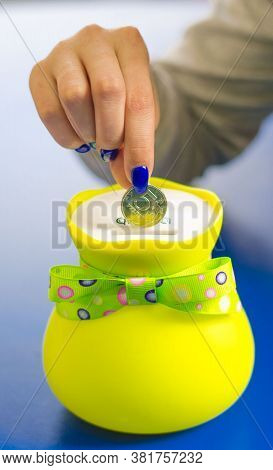 A Woman's Hand Puts A Coin In A Beautiful Bright Piggy Bank. Saving Money. Thrift. Frugality.