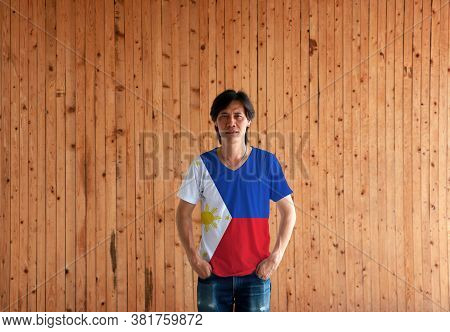 Man Wearing Philippines Flag Color Shirt And Standing With Two Hands In Pant Pockets On The Wooden W