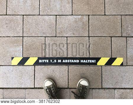 Bitte 1, 5 M Abstand Halten - German For Please Keep 1.5 M Distance - Line Marking On Sidewalk - Soc