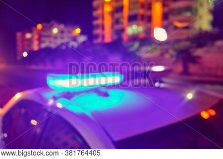 Police Car Flashing Lights In The Night Blurred Defocused