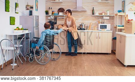 Disabled Man In Wheelchair Opens Refrigerator While Wife Is Cooking And Gives Her Box Of Eggs. Guy W