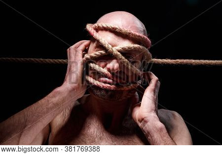 Portrait Of Binded Bald Man Trying Tear The Rope On Face