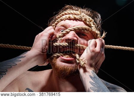 Image Of Binded Tattooed Man Trying Tear The Rope On Face
