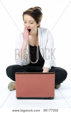 Young woman sitting on floor yawning bored with laptop isolated
