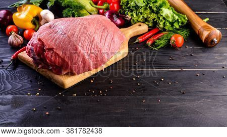 A Large Piece Raw Pork Meat Part Of The Hip, Hip Or Tenderloin On A Black Wood Background With Veget