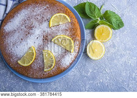 Uncut Freshly Baked Lemon Pie, Tart Or Semolina Cake On Blue Plate Served Lemon Wedges And Mint. Hom