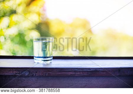 Pure Fresh Water In Glass Glass On A Wooden Table On A Green Natural Background