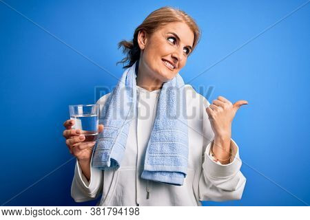 Middle age beautiful blonde sportswoman wearing towel drinking glass of water to refreshment pointing and showing with thumb up to the side with happy face smiling