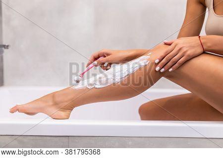 Young Woman Ahaving Long Legs With Razor In Bathroom