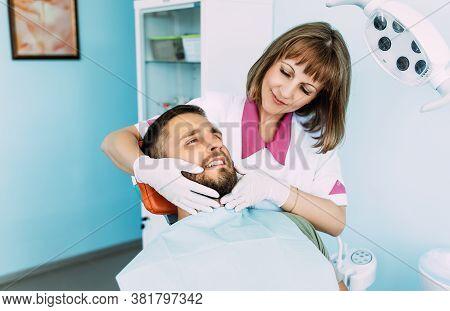 A Man Treats His Teeth At The Dentist. Dental Examination At The Dentist. A Snow-white Smile. A Youn