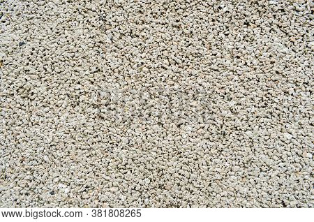 Close-up Of Texture Of Small Stones Or Gravel. Concrete Surface With Copy Space. Construction And Bu