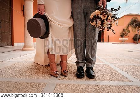 A Newly Married Couple Show Their Shoes Out Of Church. Changing Roles.