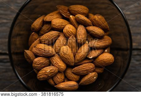 Almonds In A Small Plate On A Vintage Wooden Table. Almond Is A Healthy Vegetarian Protein Nutritiou
