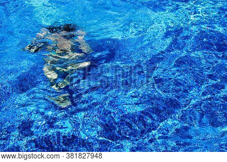 Girl In Swimsuit Under Water Dives In The Pool With Blue Tiles On Vacation. A Man Swims In A Pool Wi