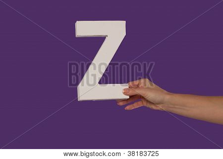 Female Hand Holding Up The Letter Z From The Right