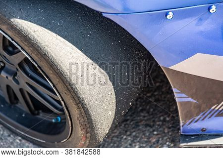 Close-up Of A Sports Car Wheel With A Worn Out Slick Tire And A Blue Bumper In The Sun. Horizontal O