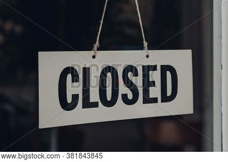 Black And White Closed Sign On A Glass Front Door Of A Restaurant.