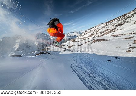 Skier Athlete In An Orange Suit And With A Backpack Jumps From A High Snowy Slope Against The Backdr