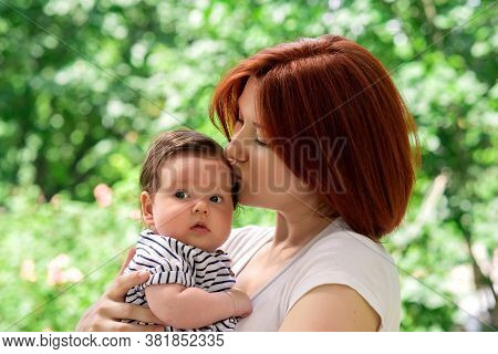 Mother Holding In Arms Infant Daughter In Striped Dress Outdoors. Baby Girl Is A Little Scared And L