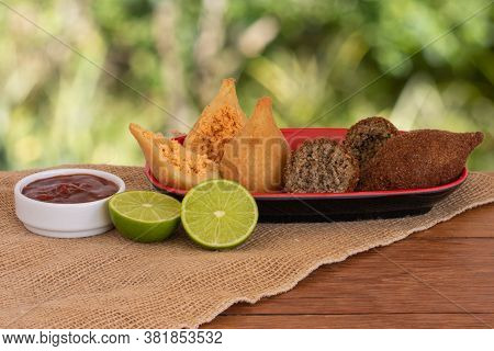 Coxinha And Kibe. Traditional Fried Brazilian Food. Background With Defocused Green. Space Copy