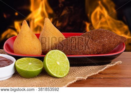 Coxinha And Kibe. Traditional Fried Brazilian Food. Background With Defocused Fire. Space Copy