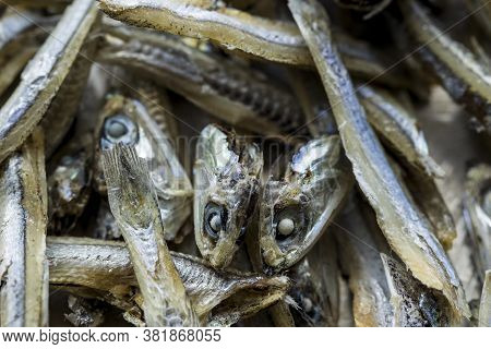 Dried Anchovy Heads And Bodies. An Overhead Macro Shot Of Dried Anchovies In A Pile.