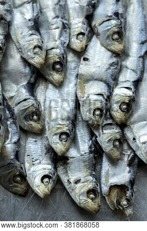 Overhead View Of Dried Sardines. An Overhead Close Up Photo Of Dried Sardines Laid In A Neat Pile.