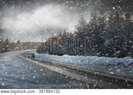 The Car Drives On A Slippery Road In Winter During A Snowfall