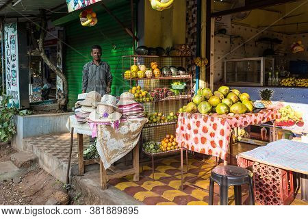 Candolim, North Goa, India - November 23, 2019: Local Street Vendor Sells Fresh Fruit And Hats In Ca