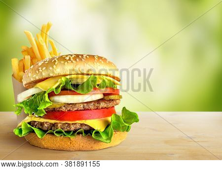 Fresh Double Hamburger And French Fries On Green Nature Background. Copy Space