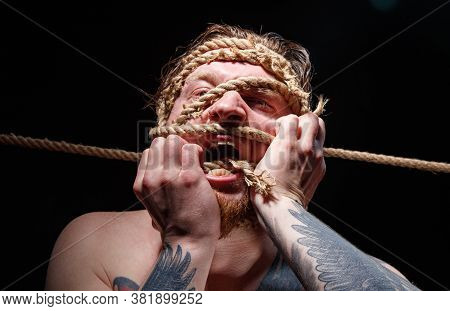 Photo Of Binded Tattooed Man Trying Tear The Rope On Face