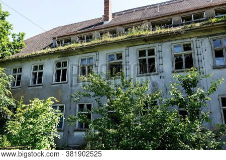 Facade Of A Abandoned Damaged Building With Trees