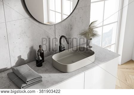 Top View Of Modern Sink With Round Mirror Standing In Modern Bathroom With White And Tiled Walls And