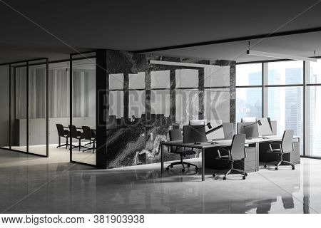 Corner Of Modern Open Space Office With Panoramic Window, Black Marble Walls And Rows Of Computer Ta