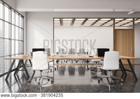 Interior Of Modern Open Space Office With White Walls, Concrete Floor, Wooden Computer Tables And Me