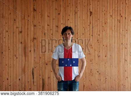 Man Wearing Netherlands Antilles Flag Color Shirt And Standing With Two Hands In Pant Pockets On The