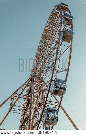 Ferris Wheel In An Amusement Park. Bottom View Of The Ferris Wheel. Attraction.