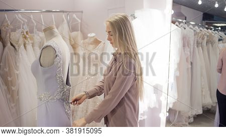Hostess Of The Wedding Salon Looks At The Wedding Dress. Small Business, Business Woman With Her Own