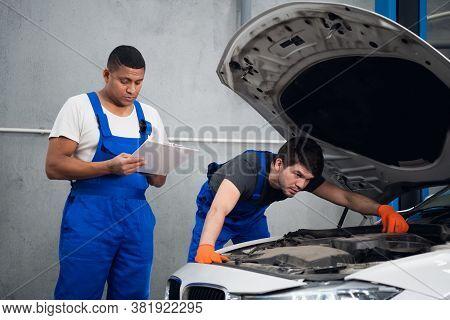 A Man Examines A Broken Car. His Partner Takes Notes
