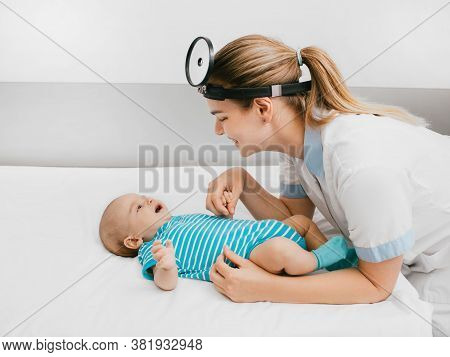 Smiling Pediatrician Communicate And Playing With Baby At The Hospital. Doctor Examines Infant Baby