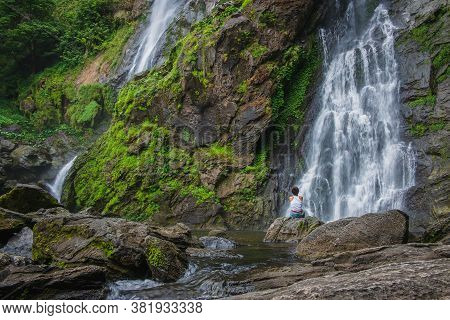 Woman Sits On A Rock With A Waterfall In Front Of Him In Klong Lan National Park, Thailand.